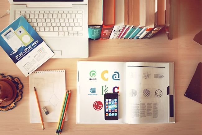 still life image of a desk with Mac products, colored pencils, books, etc