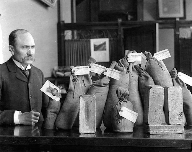 vintage image of a man looking at bags of gold
