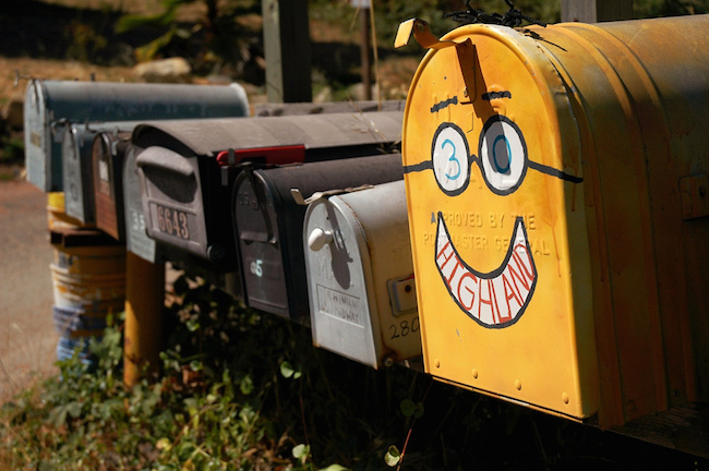 a row of mailboxes, the largest one is bright yellow with a painted smiley face