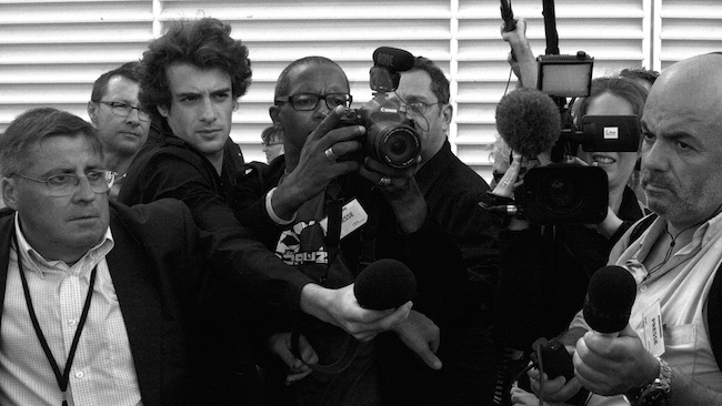 group of reporters with cameras and microphones eager to interview a source