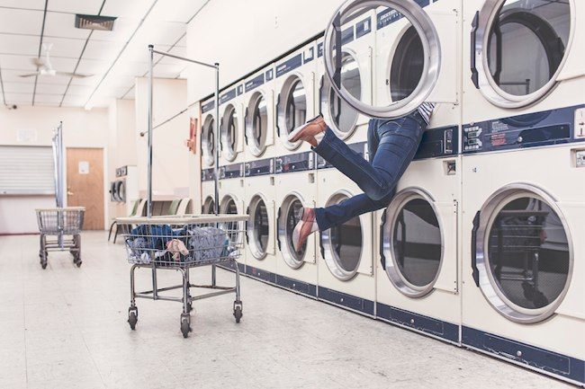 in a laundromat, a man has his upper-body stuck in a dryer, his legs are flailing outside the machine