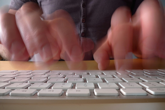 fingers in motion typing fast on a keyboard