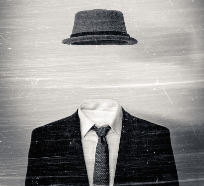 black and white image of an invisible man with no face, only a hat and suit