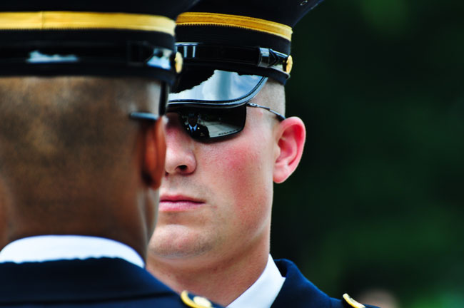 Sgt Benton Thames inspects a sentinel before the sentinel begins his walk on the mat at Arlington National Cemetary.