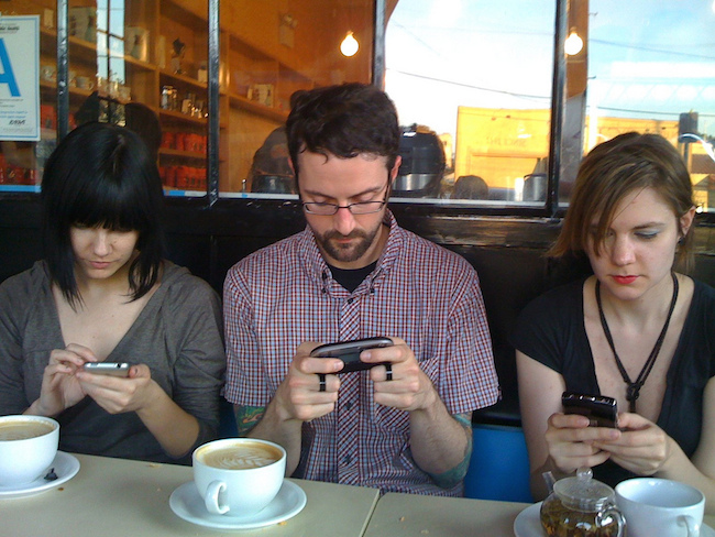 three people, each holding and looking down at a different mobile device