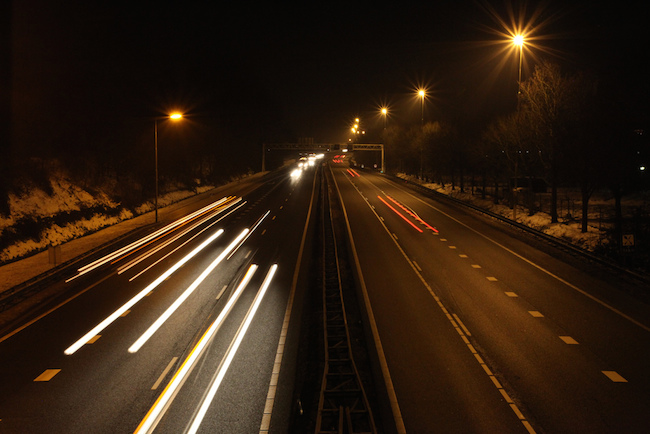 image of street at night with one lane going fast and the other slow