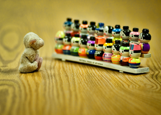 image of tiny stuffed animal and little toy people arranged to look like the animal is addressing the group