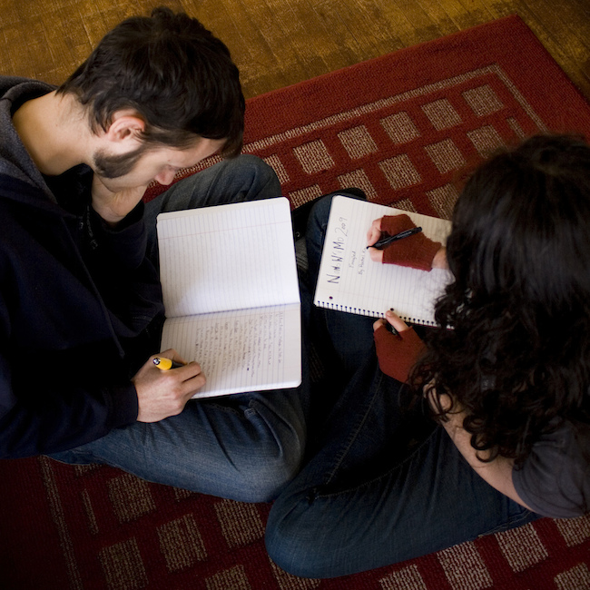 man and woman sitting on floor writing in lined notebooks