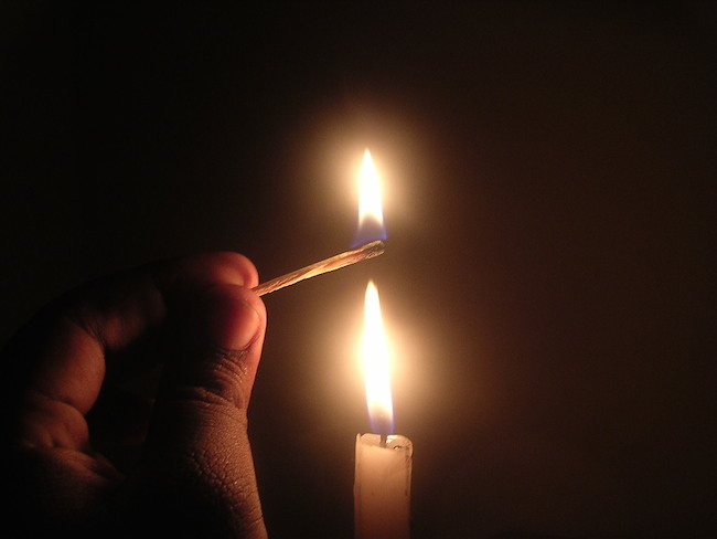 fingers holding a lit match directly above a lit candle