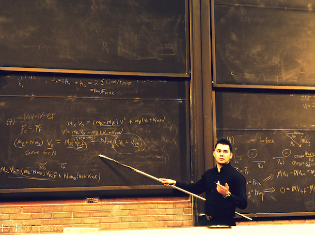 image of a man at a chalkboard with a long pointer