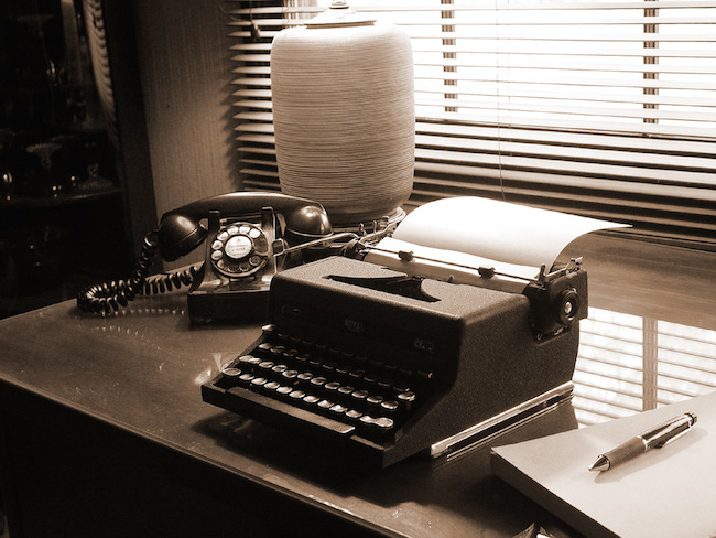typewriter centered on a desk with a telephone and pad of paper and pen