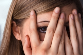 image of woman hiding behind fingers