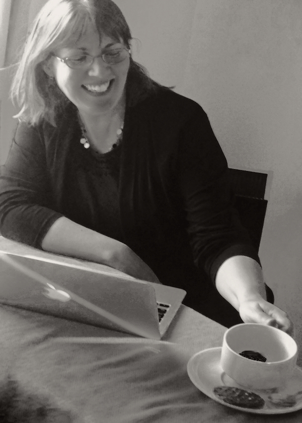 image of the author at her computer with a cup of coffee