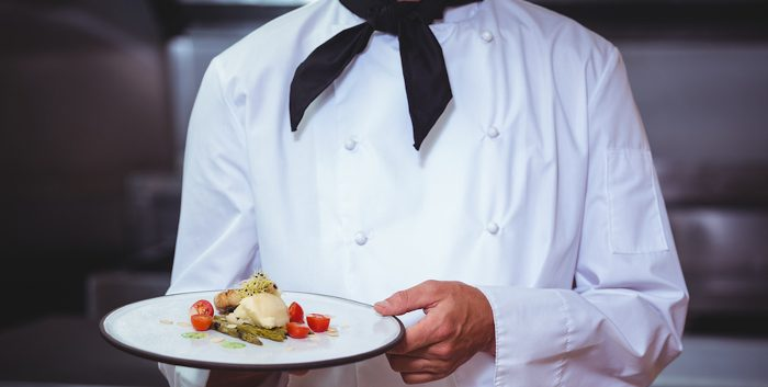 Proud chef holding a plate in a restaurant