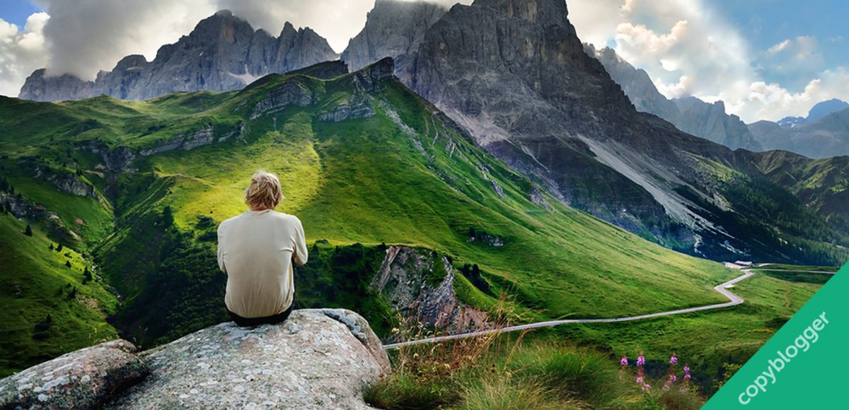 man sitting and overlooking green mountain top